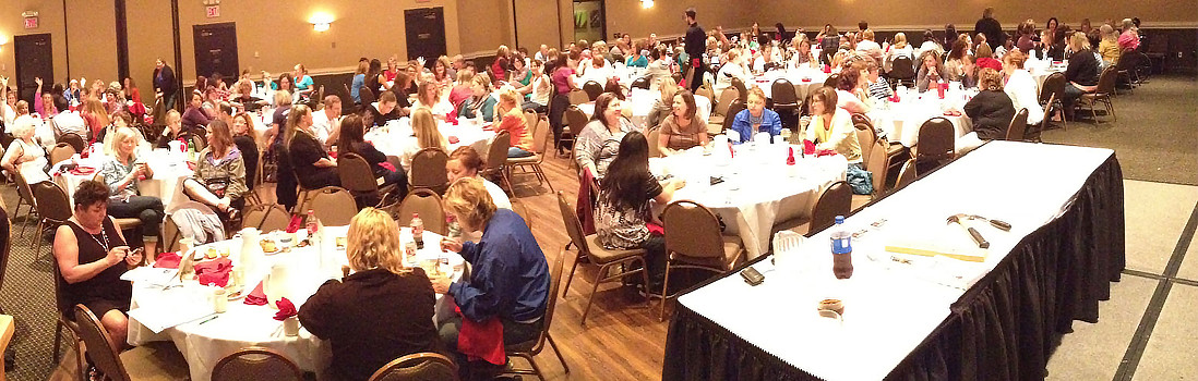 A photo of the a MFWCAA conference dinner featuring many people sitting down in a conference room.